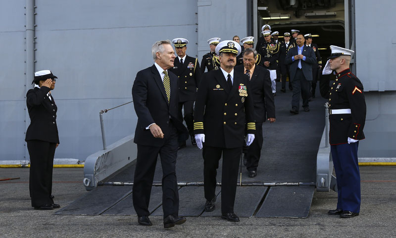 Secretary of the Navy Ray Mabus, front left, and USS America Commanding Officer Navy Capt. Robert Hall Jr., exit the ship for her Commissioning Ceremony during San Francisco Fleet Week, Oct. 11, 2014. Hall, along with Executive Officer Navy Capt. Wayne Baze, and other officers within America's wardroom, all share a Naval Postgraduate School degree in common.