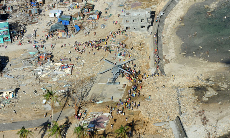 Philippine citizens gather around an MH-60S Sea Hawk helicopter from the Golden Falcons of Helicopter Sea Combat Squadron 12 as it delivers relief supplies in support of Operation Damayan.