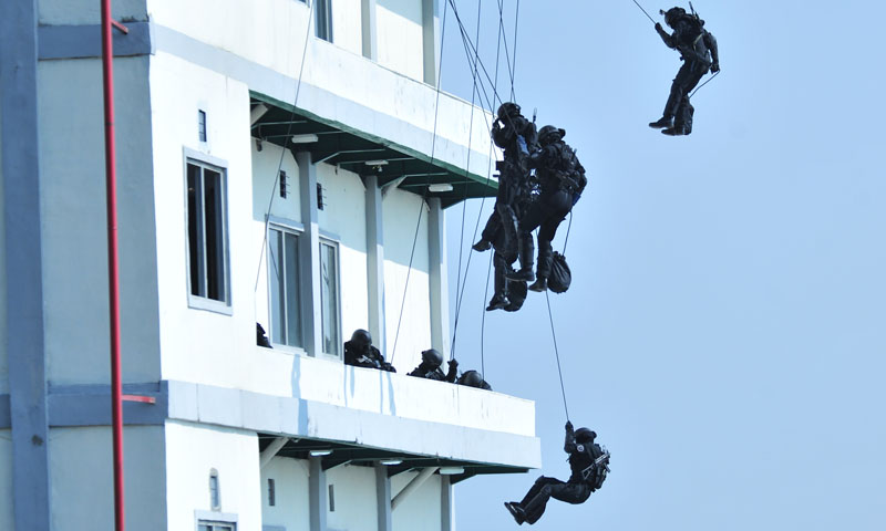 Members of an elite Indonesian counterterrorism group repel down the front of a building during a multinational counterterrorism exercise in Sentul, Indonesia. NPS' Center for Civil-Military Relations played a lead role in designing the exercise, helping develop regional capacity through a multinational approach to combating terrorism. (Photo courtesy NPS Center for Civil-Military Relations)
