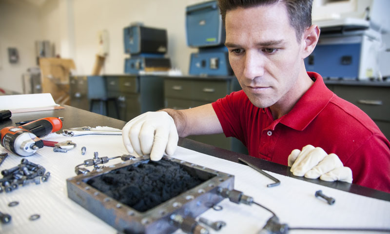 Lt. Will Curtin, a student in the mechanical engineering program, demonstrates the carbon nano-fiber foam (CFF) following its creation in the NPS Functional Materials Laboratory.