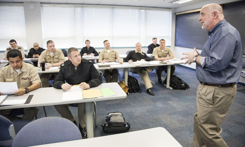 Naval Postgraduate School Department of Operations Research (OR) Professor Thomas Lucas reviews a recent exam with OR and mathematics students during his advanced statistics class, March 19. Hughes has been a member of the NPS faculty since 1998, following six years with the RAND Corporation in addition to a several years with Hughes Aircraft Co.