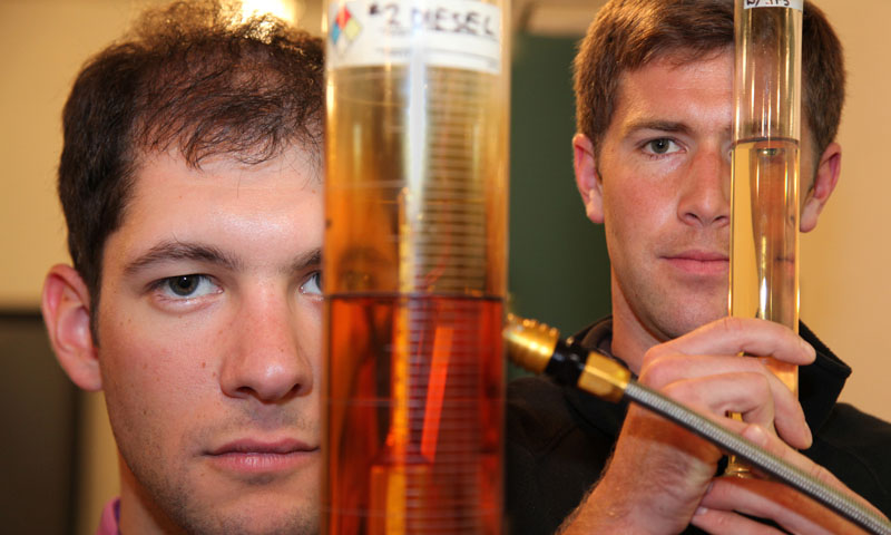 Naval Postgraduate School students Coast Guard Lt. j.g. Adam Paz and Navy Lt. j.g. John Petersen hold beakers of blended fuels that will be tested in various engines. The two students are collecting fuel efficiency data to determine best blend for various biofuels that can run in conventional and modified diesel and jet engines. Petersen is a member of NOAA Corps.