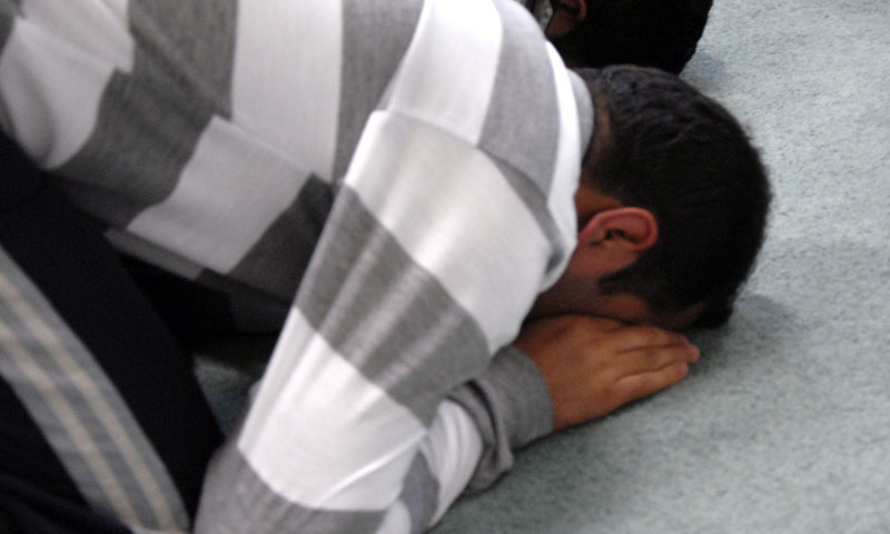 An un-named member of the Masjid al Taqwa community bows his head in prayer during a Ramadan service attended by international students studying at the Naval Postgraduate School.