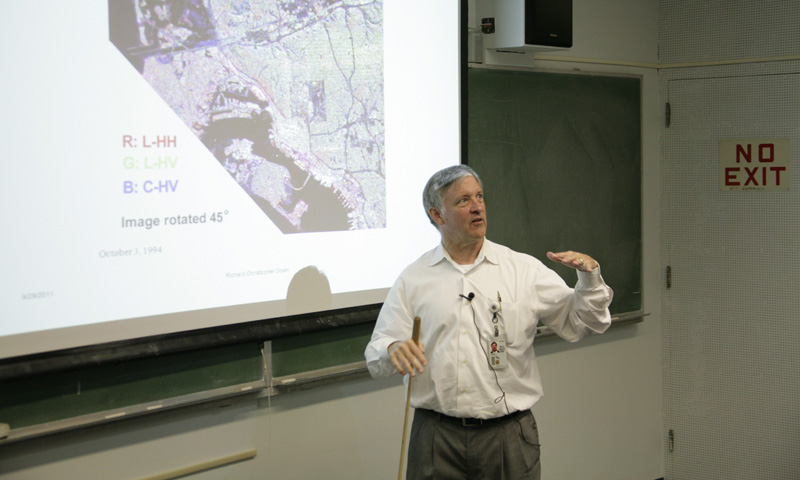 NPS Physics Professor Richard Olsen conducts class with a packed house, among them the 20 students in the new remote sensing intelligence program. Roughly half of the courses in the program are new, developed specifically to prepare students for applying their remote sensing education within the defense community.
