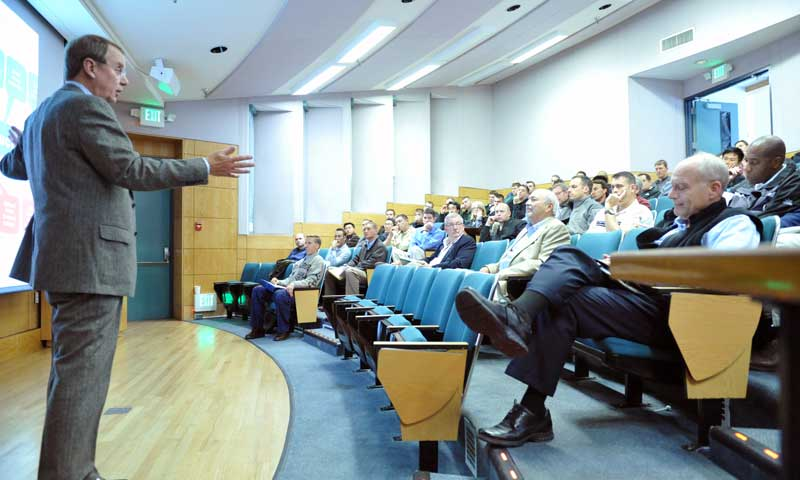 """Retired Vice Adm. Joseph Dyer, iRobot Inc. Chief Operating Officer and NPS graduate, discusses how robots fall into the category of """"disruptive technologies"""" during his presentation to NPS students, staff and faculty, Nov. 3."""