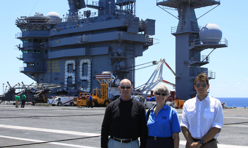 The MOVES Institute's Dr. Michael McCauley, far left, stands beside Stephanie Everett of the Office of Naval Research, and Dr. Mathias Kolsch, also of MOVES, during their visit to the USS Eisenhower to test the iPARTS software in the fleet.