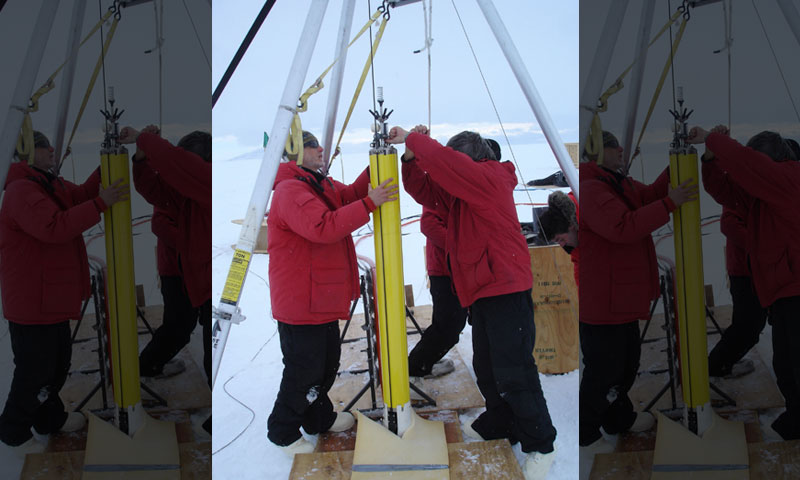 A team of researchers and NPS faculty practice lowering an ocean profiler into the ice shelf during a previous trip to Antarctica. The profiler is one of several pieces of equipment specially designed and built at NPS specifically for the current research trip.