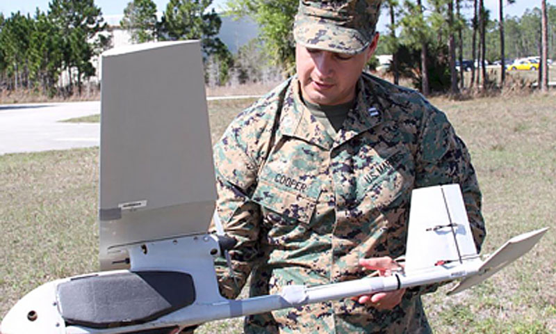 Marine Corps Capt. Dino Cooper demonstrates the ease of mounting a specially designed taggant pocket, built by NPS Professor Dr. Kevin Jones, to the RQ-11 Raven.