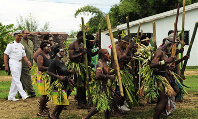 Capt. Jesse A. Wilson, is escorted into the Nakamal Chief Lodge by ni-Vanuatu customary dancers during the opening ceremony for the Vanuatu phase of Pacific Partnership 2011.