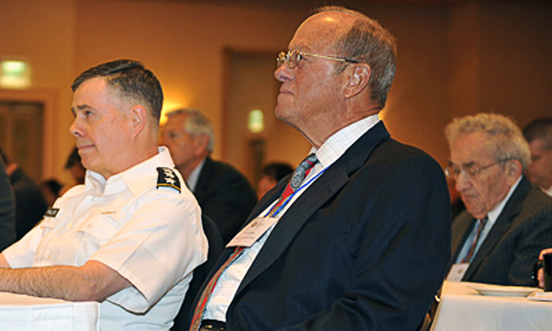 Lt. Gen. William N. Phillips, left, Principal Military Deputy to the Assistant Secretary of the Army and retired Rear Adm. Jim Greene, right, Chair of the Naval Postgraduate School's Acquisition Research Program, listen to opening remarks at the 8th Annual Acquisition Research Symposium, May 11-12 in Monterey, Calif.