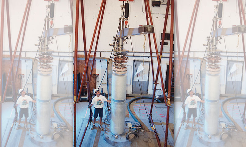 A former graduate student of Naval Postgraduate School Vice President and Dean of Research Karl van Bibber operates a crane withdrawing the Axion Dark Matter eXperiment (ADMX) experimental insert from its powerful superconducting magnet.