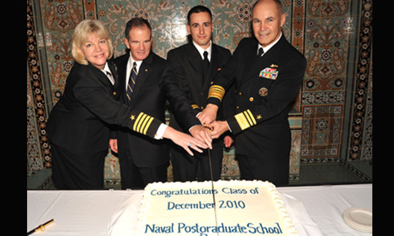 From left, Capt. Janice Wynn, President Daniel Oliver, Lt. Alexander Baynes, and Vice Adm. Richard W. Hunt take part in the ceremonial class cake cutting in a reception following the graduation ceremony on Dec. 17.