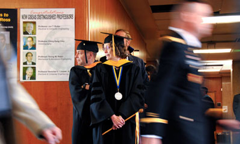 NPS faculty Fred Drake and Dorothy Denning watch as the procession of Summer 2010 graduates march past the graduation platform party in Spanagel Hall, Sept. 24.