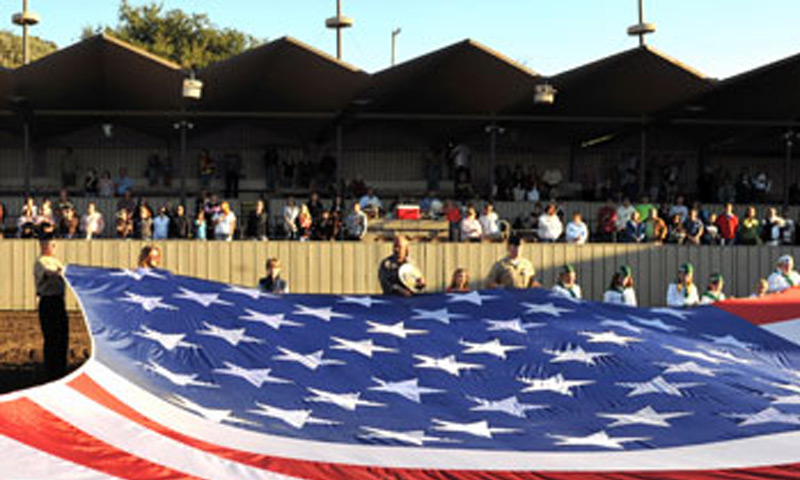 Naval Postgraduate School volunteers and members from the Monterey community unfold an American Flag at the Monterey County Fair as part of opening ceremonies for the fair's Bull-O-Rama.