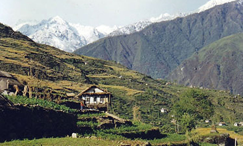 Dan Rai's two-story boyhood home with a grass roof in the remote Himalayas. Mera Peak can be seen in the background.