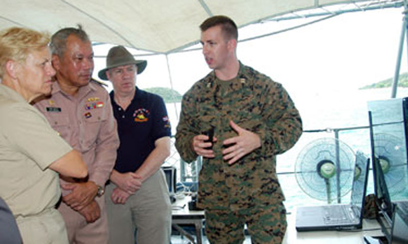 Naval Postgraduate School Information Warfare Systems Engineering student Marine Corps Capt. Carrick Longley, right, briefs the Field Information Support Tool (FIST) to Rear Adm. Nora Tyson, Commander, Combined Task Force 73 and Logistics Group Western Pacific, left, and Rear Adm. Chaiyot Sundaranaga, Commander, Frigate Squadron 2, of the Royal Thai Navy, second from left, as NPS Information Sciences Research Associate Jim Ehlert, second from right, looks on in a CARAT Thailand 2010 Tactical Operations Center at Sattahip Naval Base, Thailand, in May.