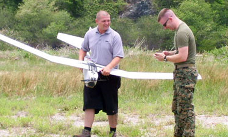 """NPS student Marine Corps Capt. Carrick Longley, right, and Mr. Aaron Aamold of unmanned aerial vehicle (UAV) manufacturer AeroVironment prepare to launch a Puma All-Environment mini-UAV during the CARAT Thailand 2010 exercise in May. The UAV relayed video images from its onboard cameras and """"human terrain"""" data collected using the Field Information Support Tool (FIST) Longley designed for his master's thesis to a tactical operations center where they were seamlessly fused for decision makers."""