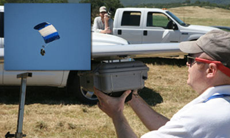 Researchers mount the Snowflake precision airdrop prototype to the wing of an Arcturus Unmanned Aerial Vehicle prior to field-testing during experiments in Camp Roberts, Calif. Once released, shown inset, Snowflake's sensor package and parafoil allow the prototype to autonomously self-guide the payload to a precise landing zone.