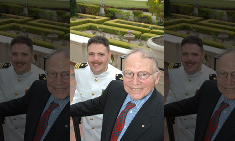 """NPS Professor Emeritus of Mechanical and Aeronautical Engineering and renowned aeronautical engineer Dr. E. Roberts """"Bob"""" Wood, right, shared a moment on the veranda overlooking the Rose Garden during the post-commencement reception with newly minted Systems Engineering graduate Cmdr. Clay Davis. Wood co-taught Davis' course in Aviation Systems Engineering."""