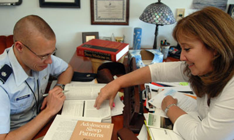 "Air Force Lt. Col. Anthony Tvaryanas, left, and Operations Research Associate Professor Nita Miller, right, review study results for Tvaryanas' doctoral dissertation on human systems integration. The chapter, ""Effects of Sleep on Training Effectiveness in Soldiers at Fort Leonard Wood,"" outlines the team's findings on matching sleep times to the body's natural rhythms, and the corresponding successes in training effectiveness."