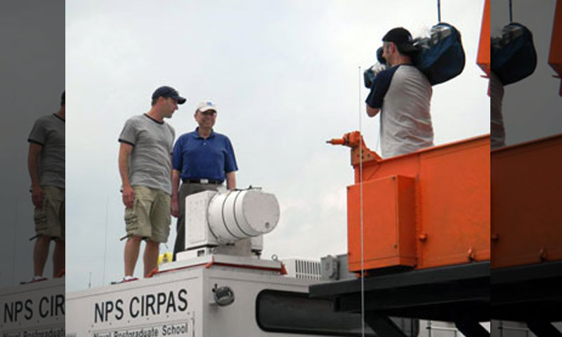 Weather Channel correspondents Mike Bettes, left, and Dr. Greg Forbes, right, film a report on top of NPS' Mobile Phased Array Radar truck. The radar system is also the subject of the cover story of the May 2010 edition of the Bulletin of the American Meteorological Society.