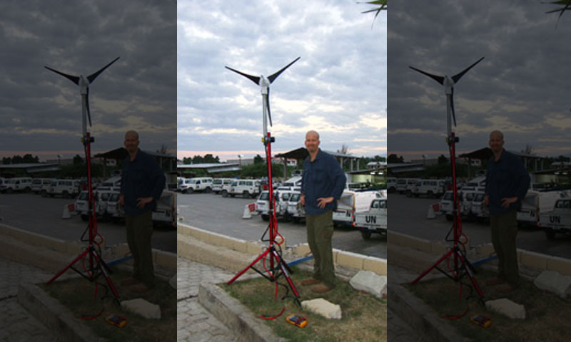 Cebrowski Institute Research Associate Dave Nystrom, a retired Navy Supply Corps commander working at the Office of Naval Research, stands next to a wind turbine at the group's camp near the U.S. Embassy.