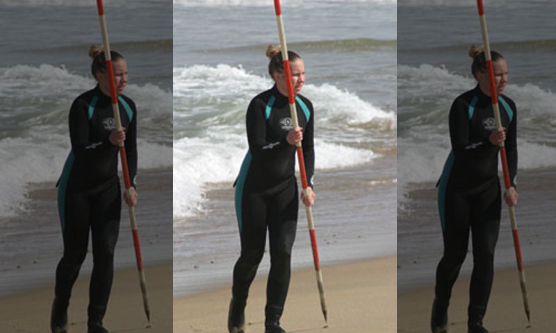 Oceanography Ph.D. student Jenna Brown holds a beachmarker during a rip current field experiment in the surf zone near the Naval Postgraduate School.