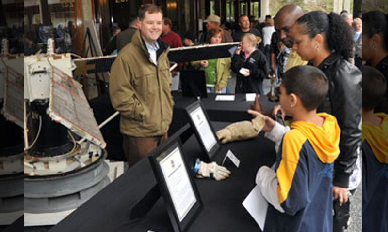 Lt. Cmdr. Hank Travis, a Space Systems Operations student, describes the NAVSAT, or Navy Transit Satellite, to an attending family. The U.S. Navy Transit Satellite is one element of a worldwide navigational system that has been in operation by the Navy for over 40 years.