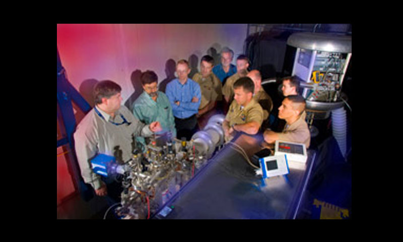 Students and faculty review the recently acquired free electron laser prior to a test firing in its new dedicated directed energy laboratory. NPS faculty expect FEL technology to be placed into the Innovative Naval Prototype (INP) program, an endeavor which the Office of Naval Research dedicates 10 percent of its annual budget to advanced research on futuristic technologies.