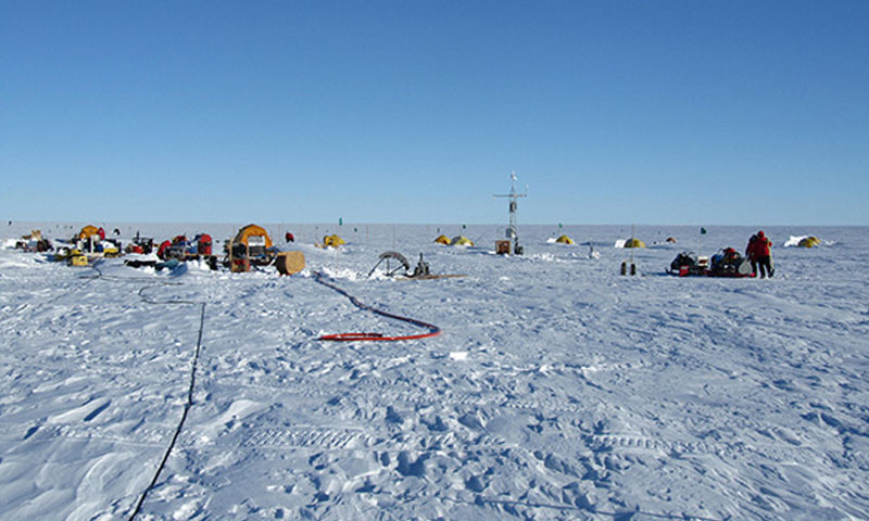 The drill camp at the Pine Island Ice Shelf. The galley is on the left, hot water drill equipment in the center left, surface infrastructure tower mid right, and the seismic sled on the right.