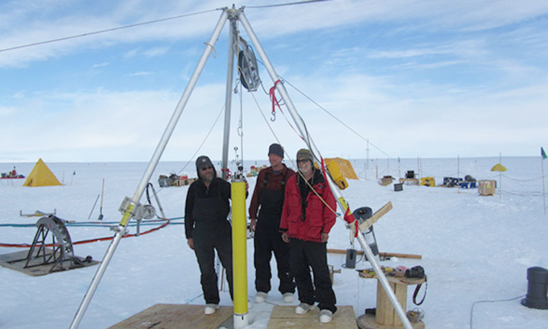 NPS research team members Stanton, Shaw and Stockel deploy the ocean flux profiler developed in their research group at NPS  down a 460m deep bore hole through the Pine Island Glacier Ice Shelf. The profiler will measure temperature, salinity and current profiles through the water cavity below the ice shelf every day day over the next two years to study processes controlling ocean melting of the ice shelf.