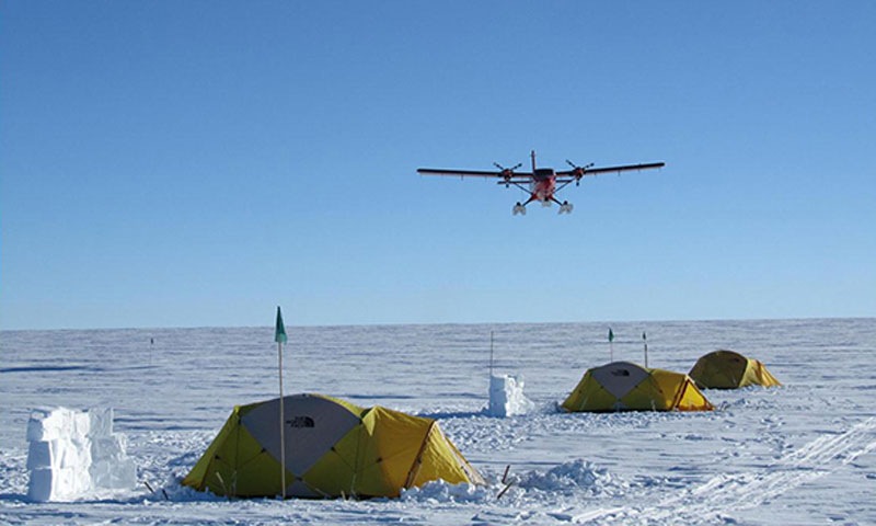 The Twin Otter approaches low over the drill camp, bringing equipment from the support camp 50 miles up from the ice shelf.