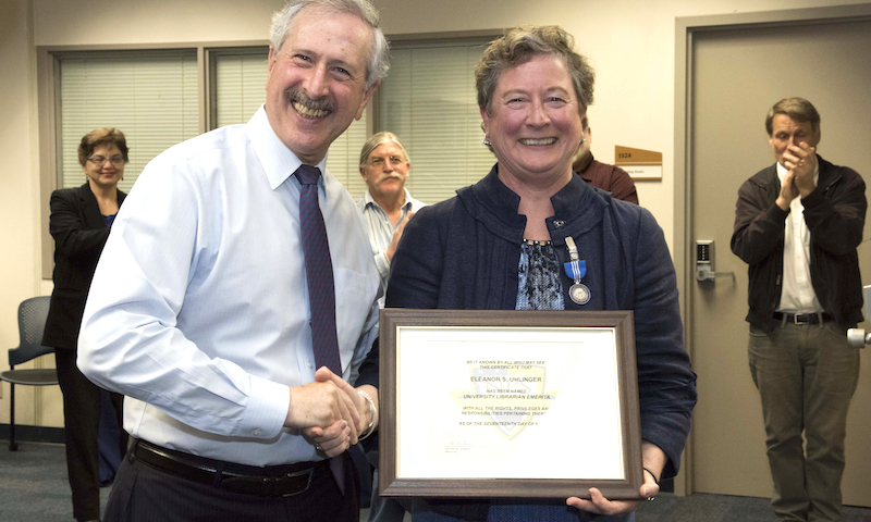 University Librarian Eleanor Uhlinger, right, is presented with a certificate by NPS Provost Dr. Steve Lerman