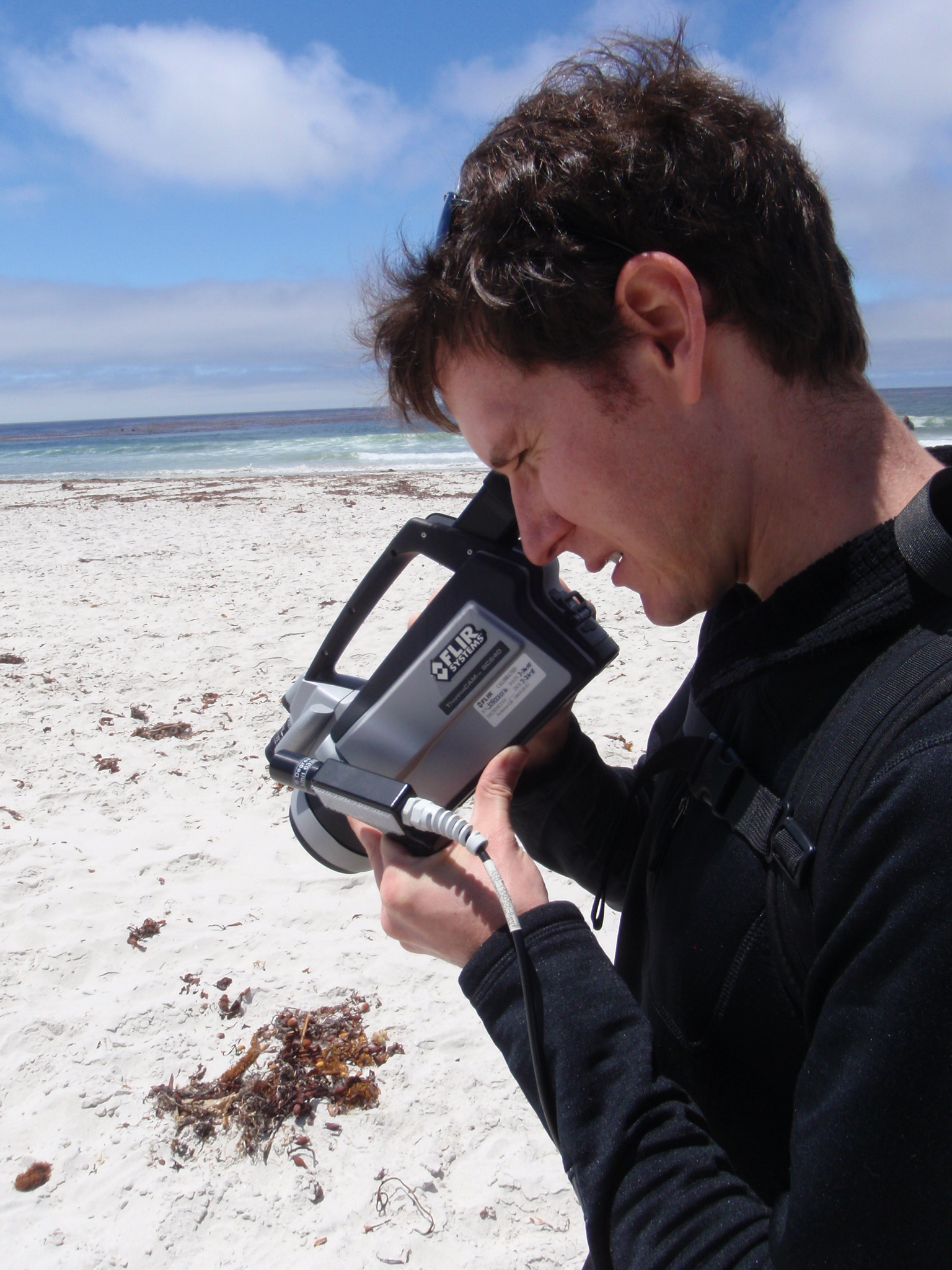 Dr. Chad Brodel uses an infrared camera on a beach in Carmel, CA to determine temperatures as a sensor on an airplane simultaneously collects imagery overhead