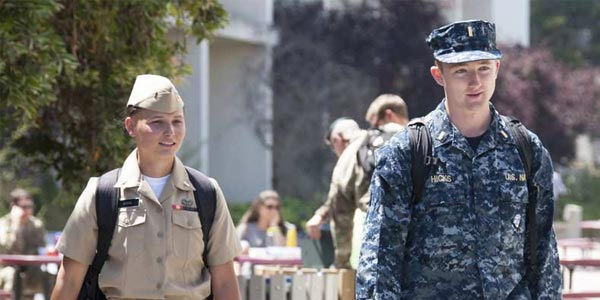Image of two uniformed Navy graduate students walking outside at NPS