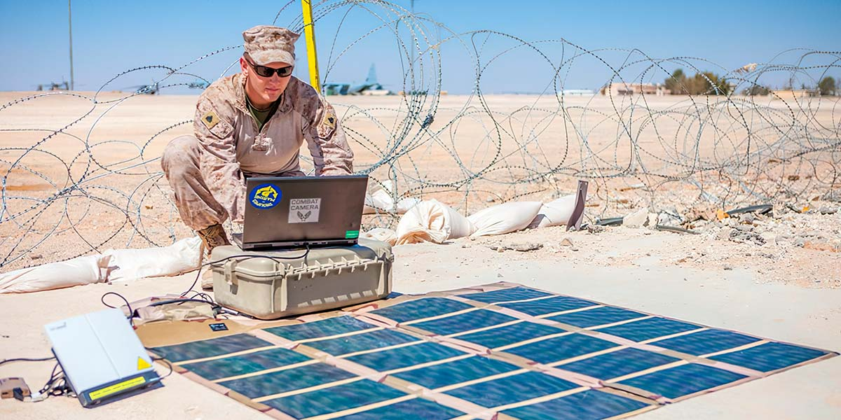 Image of a Marine soldier in a desert environment with a portable solar power array.